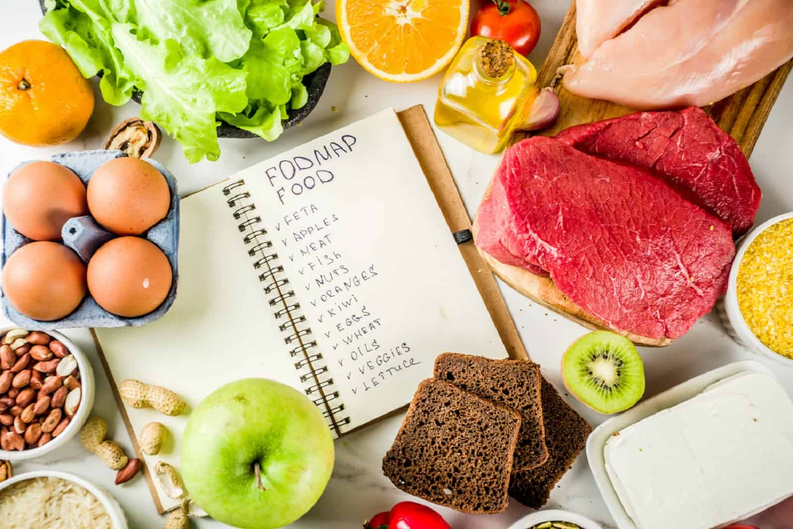 fodmap food written on a notebook,  placed on top of a marble counter with various meat, vegetables, fruits and grains