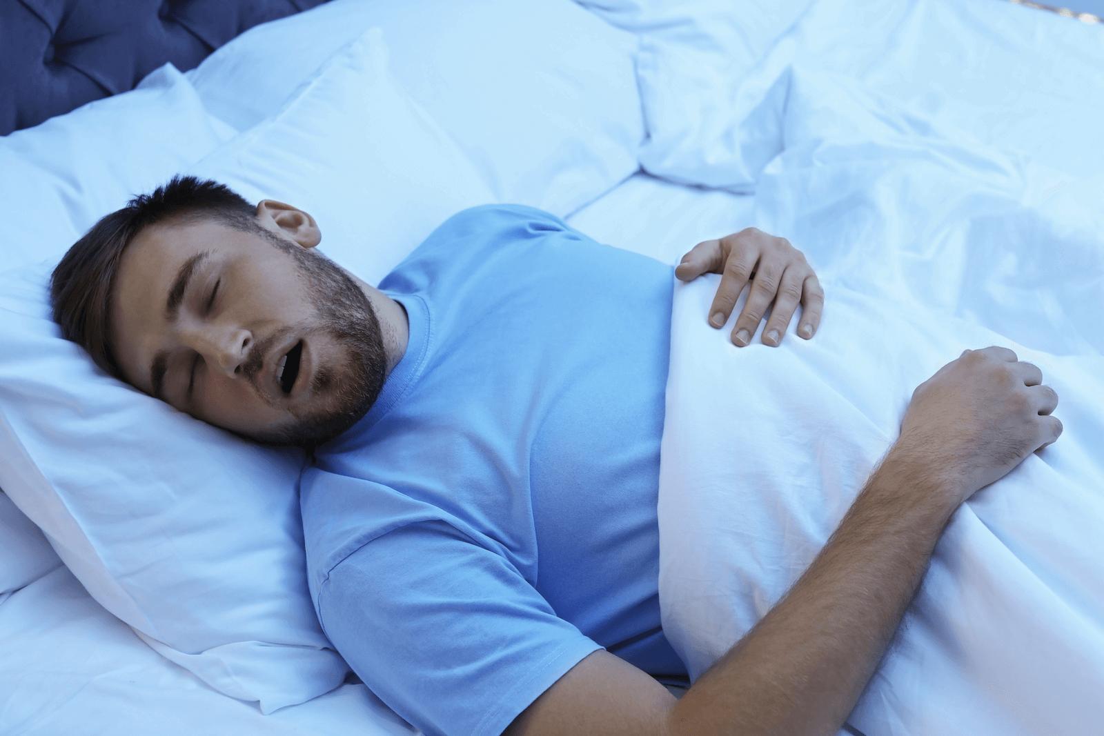 sleep efficiency: man sleeping soundly on his bed