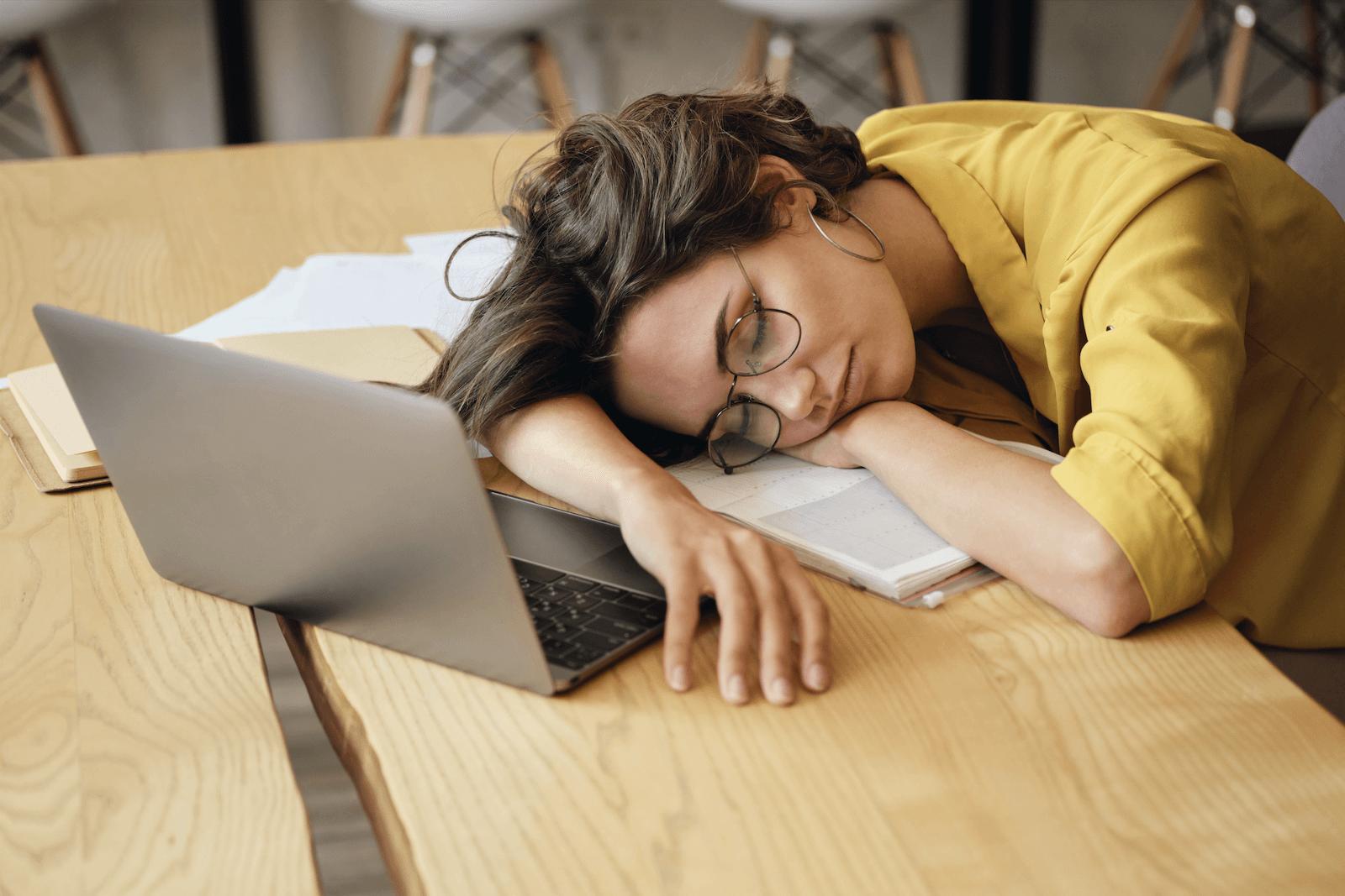 sleep efficiency: woman sleeping on table in front of her laptop