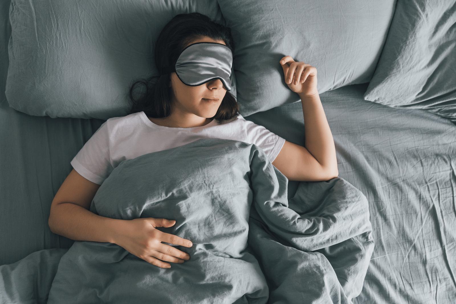 poor sleep hygiene: woman sleeping with an eye mask