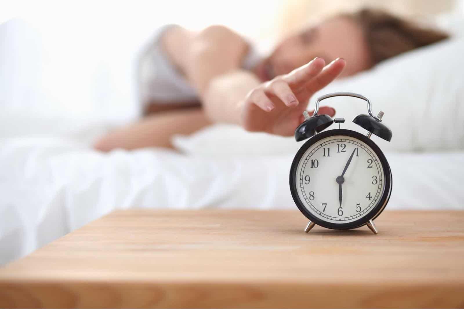 poor sleep hygiene: woman touching the alarm clock