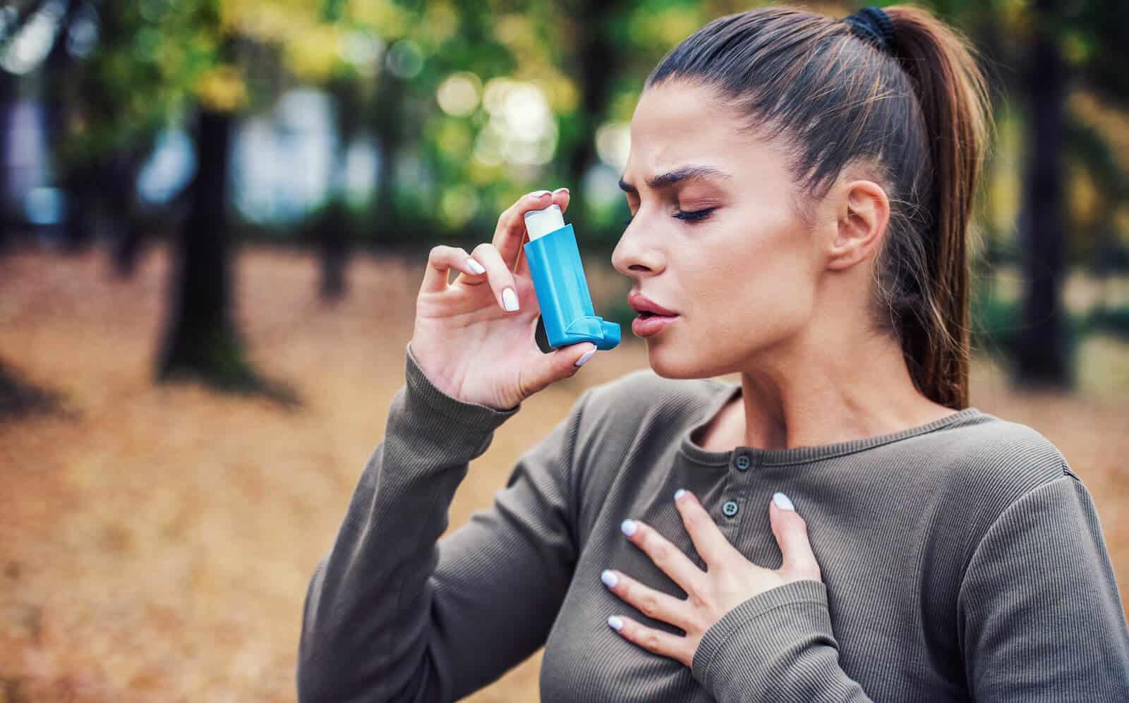 LPR symptoms: woman using an asthma inhaler