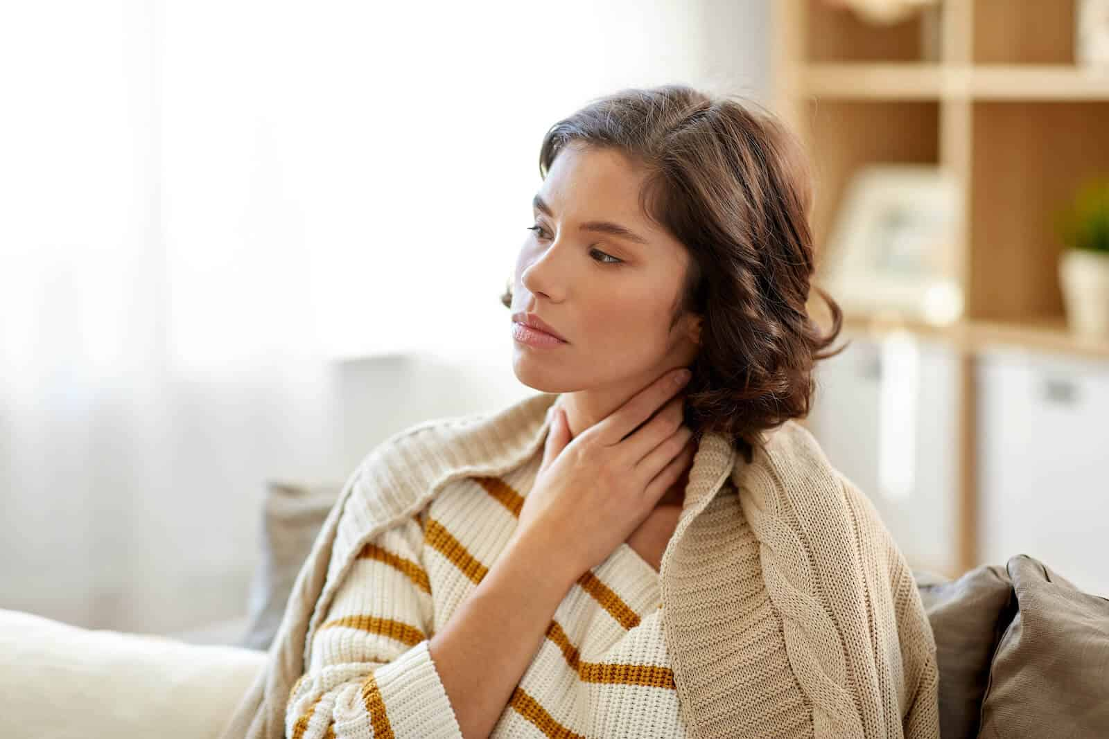 LPR symptoms: woman with a sore throat touching her neck